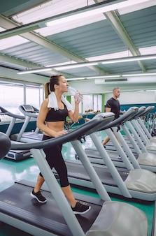 Giovane donna che beve acqua durante l'allenamento su un tapis roulant nel centro fitness