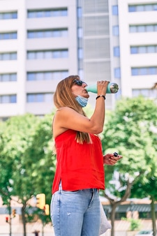 Acqua potabile della giovane donna mentre indossa la sua maschera. concetto di nuova normalità e lotta al virus.