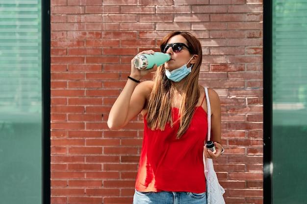 Acqua potabile della giovane donna mentre indossa la maschera