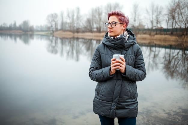 La giovane donna beve la tazza di caffè sulla riva del lago