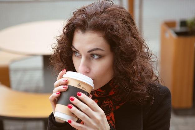 Una giovane donna beve caffè caldo sulla terrazza di un ristorante di strada
