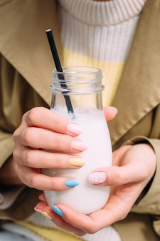 Una giovane donna beve un frullato all'aperto da un elegante barattolo di vetro con una cannuccia