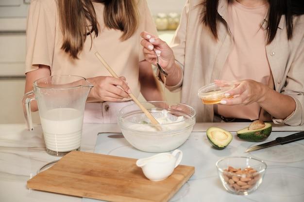 Giovane donna che gocciola miele nella ciotola di vetro con il latte mentre sua figlia mescola gli ingredienti del gelato con un cucchiaio di legno dal tavolo della cucina