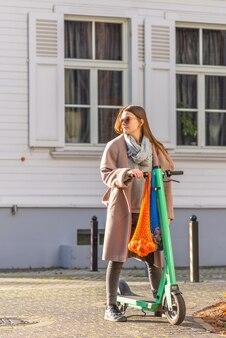 Giovane donna guida con scooter elettrico con borse a rete ecologiche