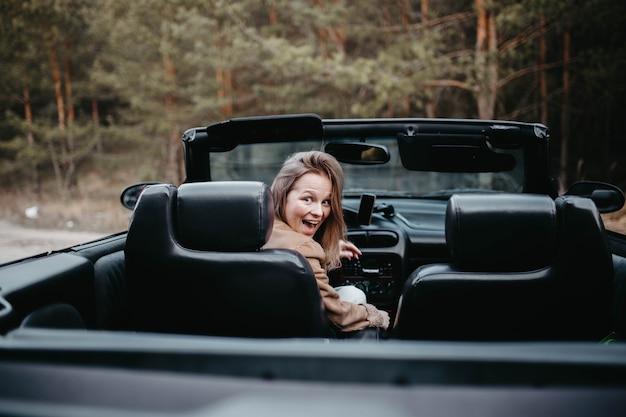 Giovane donna autista in auto decappottabile in estate