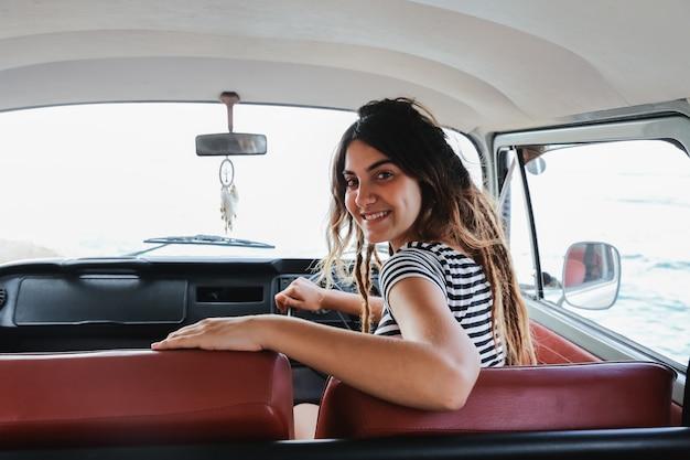 Autista della giovane donna che sorride e che guarda indietro durante il viaggio