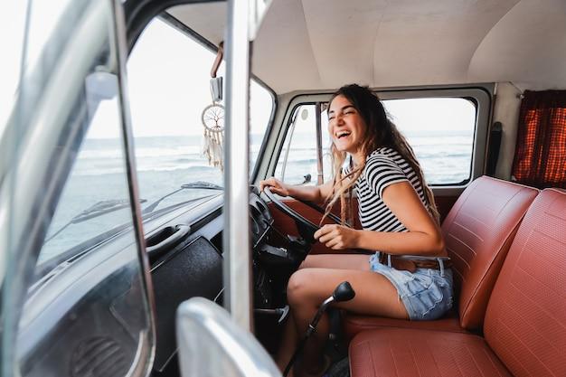 Autista della giovane donna che sorride durante il viaggio