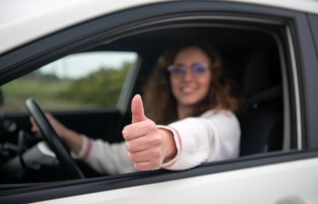 La giovane donna che guida sta facendo un pollice in alto gesto con la sua mano