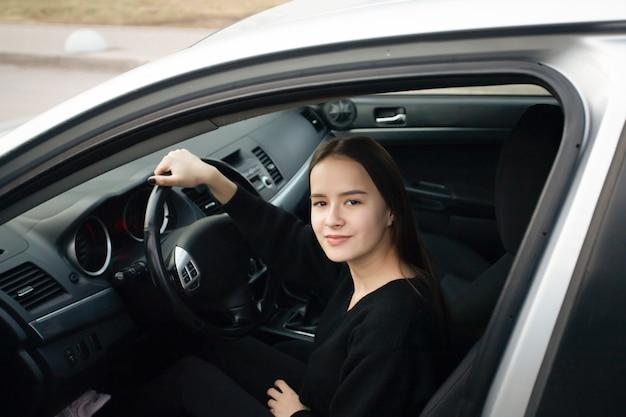 Giovane donna in una scuola guida, imparare a guidare, seduto in una macchina, sorridente