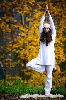 Giovane donna durante una pratica yoga nella natura autunnale
