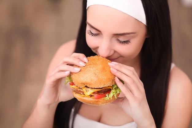 La giovane donna mangia un hamburger