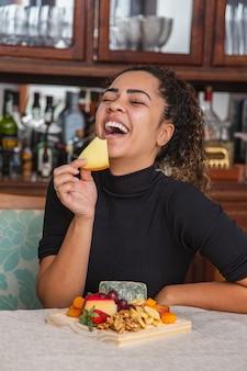 Giovane donna che mangia formaggio. donna che mangia snack al formaggio