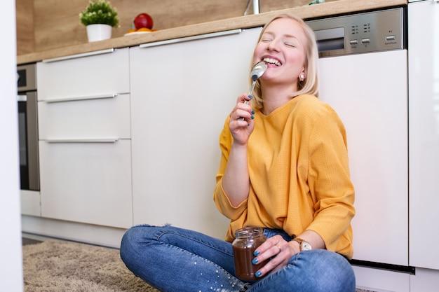 Giovane donna che mangia cioccolato da un barattolo mentre sedendosi sul pavimento della cucina in legno. ragazza carina albina indulgere faccia insolente mangiare cioccolato si diffuse dal barattolo usando il cucchiaio assaporando ogni boccone