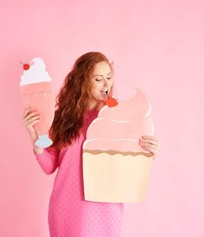 Giovane donna che mangia un cupcake allo scatto in studio