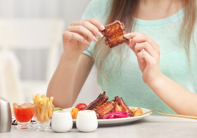 Giovane donna che mangia deliziose costolette per il pranzo nel ristorante