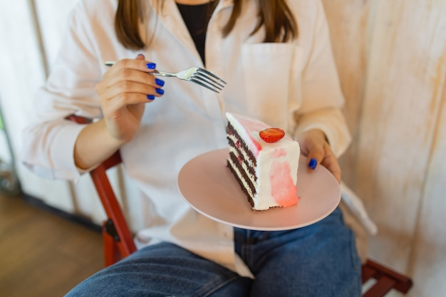 Giovane donna che mangia il dessert nel ristorante vista dall'alto del primo piano delle mani delle femmine che tengono la forcella con un pezzo di...