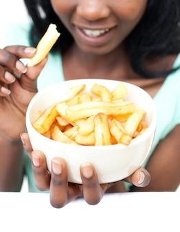 Giovane donna che mangia patatine fritte Foto Premium