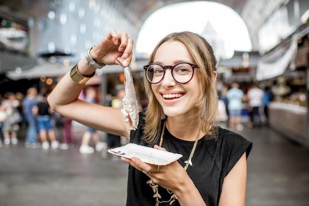 Giovane donna che mangia aringa con cipolle tradizionale spuntino olandese nel mercato di rotterdam