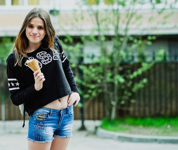 Giovane donna che mangia il gelato in una giornata di sole all'aperto, vicino alla grande casa