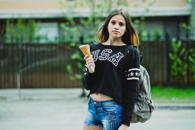 Giovane donna che mangia il gelato giornata di sole all'aperto