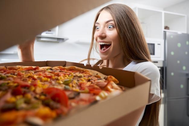Giovane donna che mangia pizza con piacere