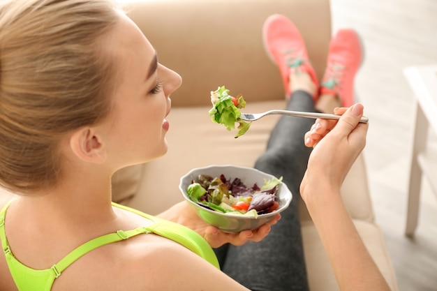 Giovane donna che mangia insalata a casa.
