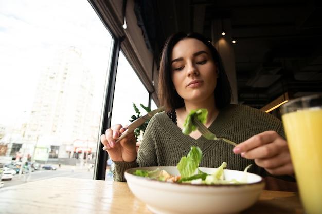 Giovane donna che mangia insalata nel ristorante. concetto di cibo sano.