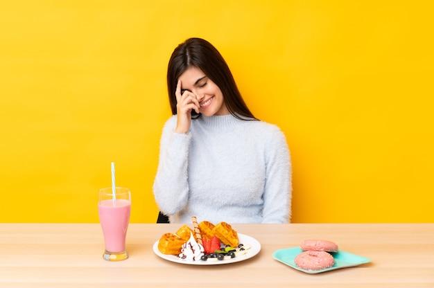 Giovane donna che mangia cialde e frappè in una tabella sopra la risata gialla isolata