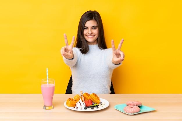Giovane donna che mangia cialde e frappè in una tabella sopra il giallo isolato che sorride e che mostra il segno di vittoria