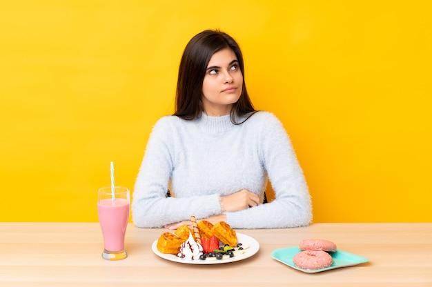 Giovane donna che mangia cialde e frappè in una tabella sopra la condizione gialla isolata e che osserva al lato
