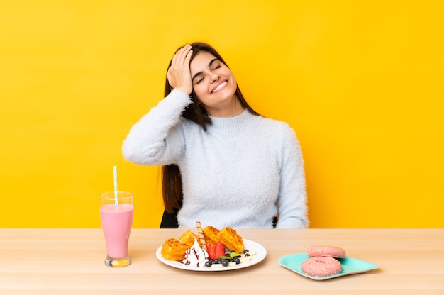 Giovane donna che mangia cialde e frappè in una tabella sopra la risata gialla isolata della parete