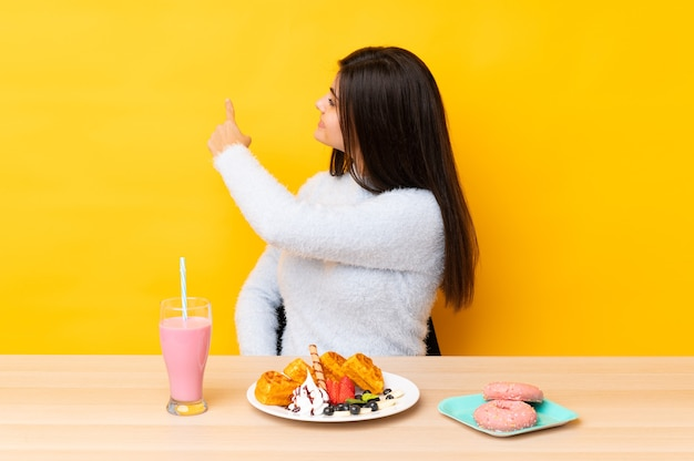 Giovane donna che mangia cialde e frappè in una tabella sopra la parete gialla isolata che indica indietro con il dito indice
