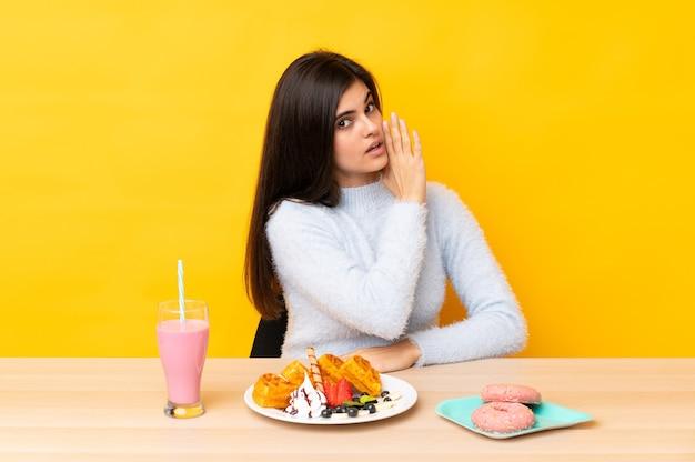 Giovane donna che mangia cialde e frappè in una tabella sopra la parete gialla isolata che bisbiglia qualcosa