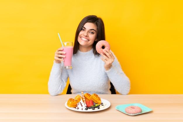Giovane donna che mangia cialde e frappè in una tabella su giallo isolato