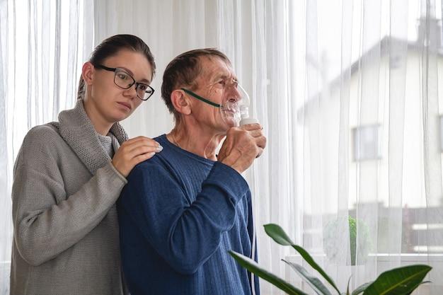 Giovane donna e anziano anziano con maschera ad ossigeno in quarantena a