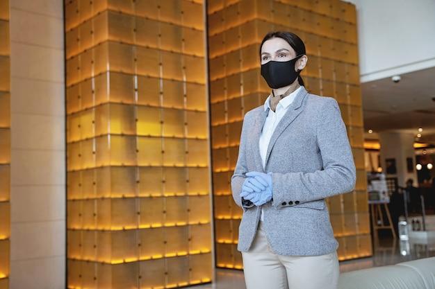 Giovane donna in abito elegante che indossa una maschera in tessuto con guanti di gomma mentre segue le precauzioni di sicurezza pandemiche