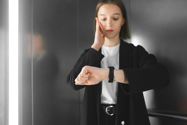 La giovane donna nell'ascensore è in ritardo.