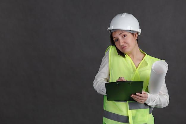 Ingegnere di giovane donna in casco protettivo e giubbotto parlando al telefono e prendendo appunti. congestione.