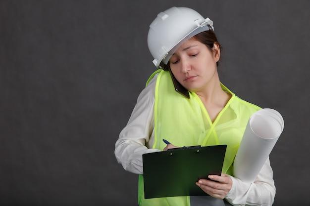 Ingegnere di giovane donna in casco protettivo e giubbotto parlando al telefono e prendendo appunti.