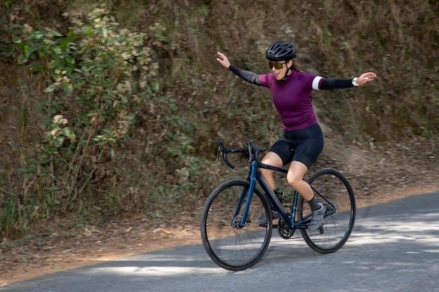 Giovane donna che si gode un giro in bicicletta all'aperto nel mezzo della foresta