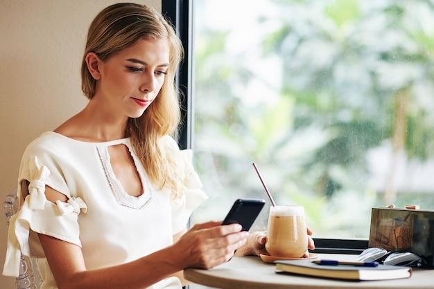 Giovane donna che gode della bevanda fredda del caffè e legge i messaggi o gli articoli di prova sullo schermo dello smartphone