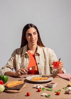Giovane donna che si gode una deliziosa pizza al calzone
