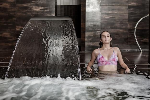Giovane donna che gode dell'idromassaggio nella piscina termale
