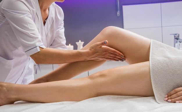 Giovane donna che gode del massaggio gambe con olio nel salone spa. cosmetologia