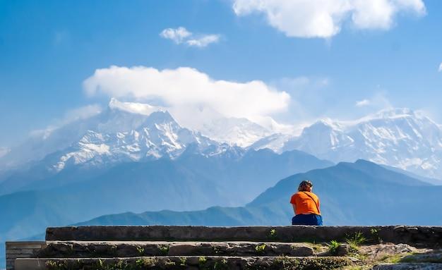 Giovane donna che gode di una montagna di machapuchare (coda di pesce) e vista della gamma di annapurna, himalaya