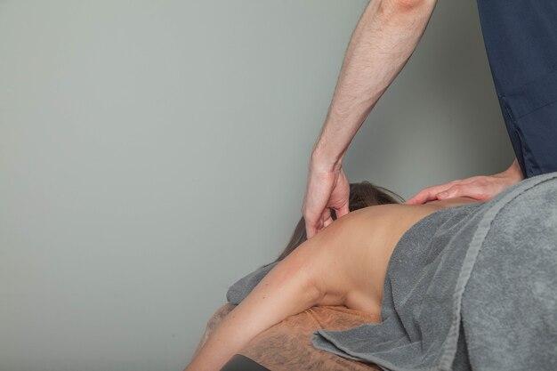 La giovane donna gode del massaggio di benessere sportivo nell'ufficio medico della sala fitness. il massaggiatore domiciliare professionista fa esercizi di massaggio. concetto di relax, bellezza, salute, cura del corpo. copia spazio