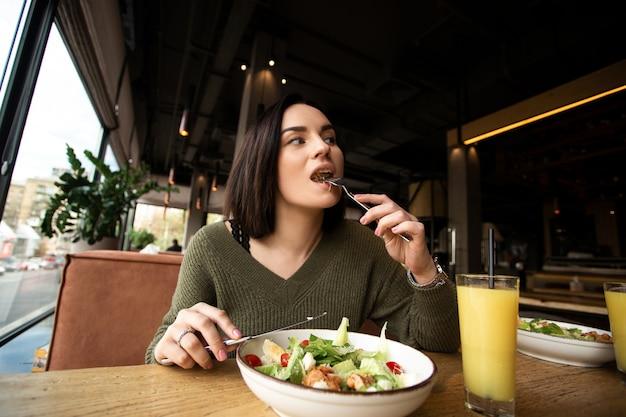 La giovane donna gode di un pasto gustoso. donna attraente con capelli castani che mangia lentamente insalata caesar sana