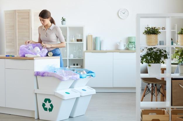Giovane donna che esamina la borsa con la spazzatura che smistano i rifiuti negli altri bidoni a casa