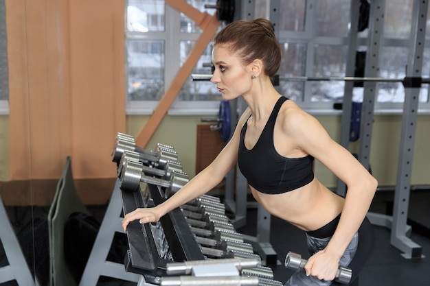 Giovane donna che si esercita con i manubri in palestra e flette i muscoli - modello di fitness muscolare del bodybuilder atletico