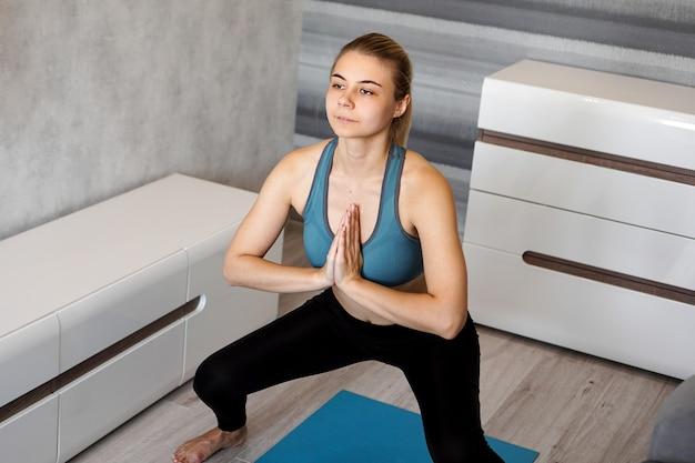Giovane donna che si esercita e che fa squat nel soggiorno di casa
